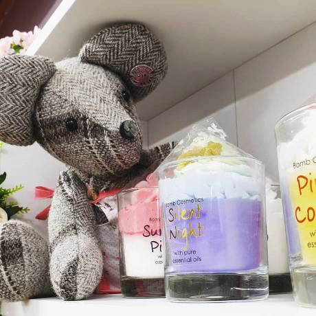 A selection of gift items including a cuddly toy and scented candles